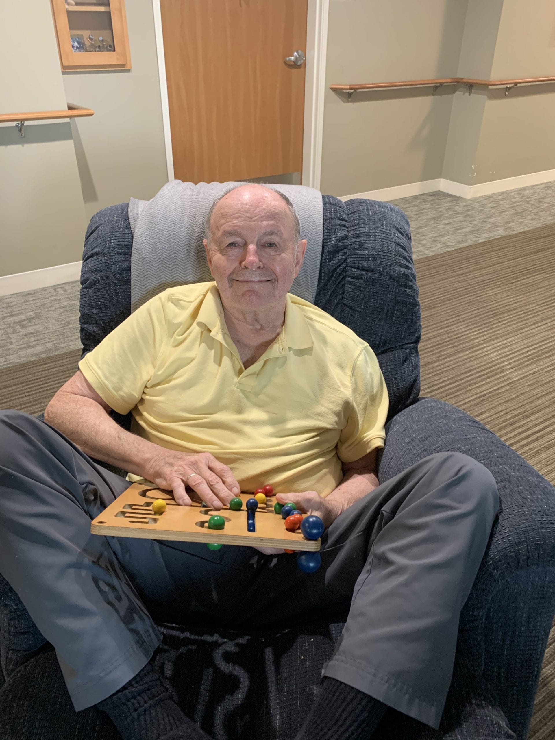 Senior man smiles while sitting in chair with board game